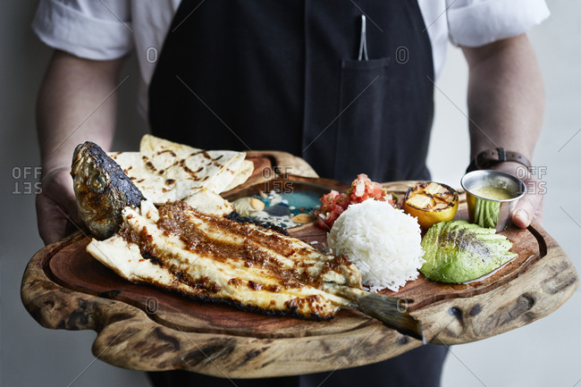 Chef holding seafood plate with whole fish