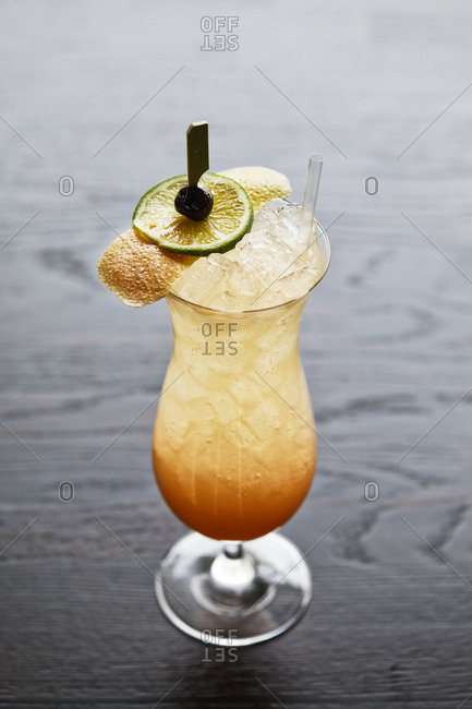 Cocktail with lime and orange peel on a dark background
