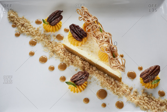 Fine dining cheesecake on white plate with pecans
