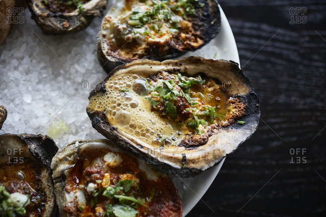 Close up of grilled oyster on a dark surface with lemon