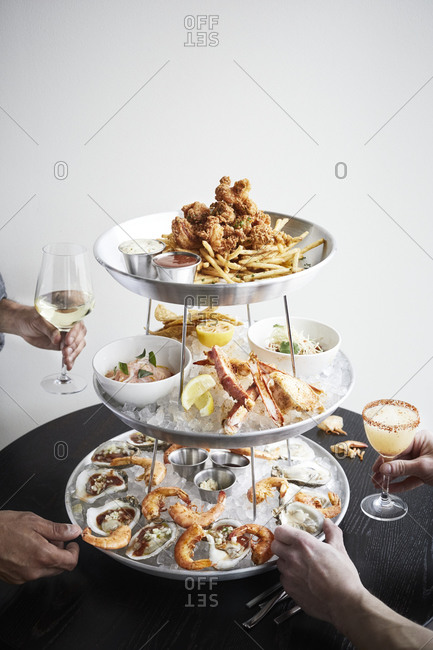 Group enjoying food from seafood tower with their cocktails