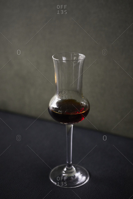 Glass of amaro on a dark table