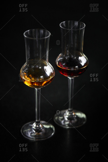Two glasses of amaro on a dark background
