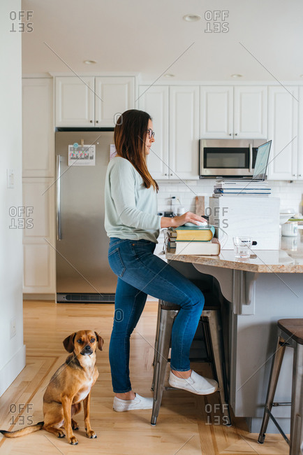 Woman working from home with a stack of books as a desk