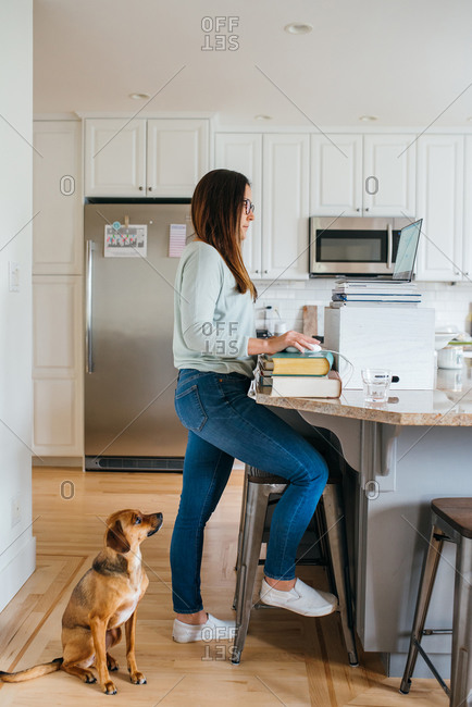 Woman working at make-shift desk in kitchen