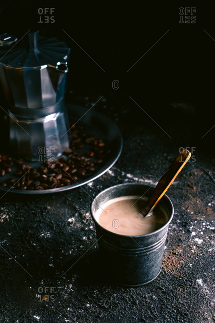 Metal cup with freshly brewed coffee and wooden spoon placed on messy black surface near tray with coffeemaker and roasted grains