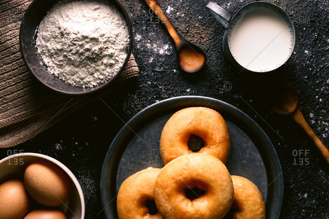Top view of fresh doughnuts placed on rough table near various pastry ingredients and utensils in kitchen
