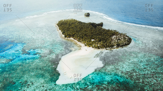Drone view of overgrown with green tropical plants island among turquoise ocean in Philippines