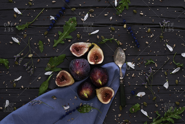 From above fresh halved figs and silver spoon placed on wooden table near blue napkin and arugula in kitchen