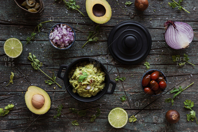Top view of various fresh ingredients placed on lumber table near pot with yummy guacamole