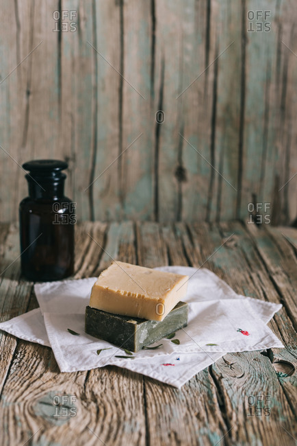 Pieces of organic soap placed on napkins near bottle of natural oil on weathered timber table