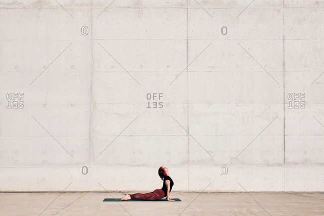 Side view of trendy fit female athlete in sportswear doing baby cobra yoga exercise on sports mat while training alone on street against concrete wall in sunny day