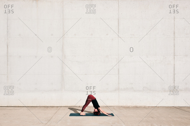 Side view of trendy fit female athlete in sportswear doing downward facing dog yoga pose on sports mat while training alone on street against concrete wall in sunny day