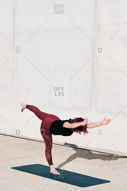 Side view of barefooted woman in sportswear doing yoga in warrior three pose on mat training alone on street against concrete wall in sunlight