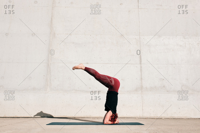 Side view of unrecognizable barefooted female athlete in activewear standing upside down in sirsasana position with legs raised on sports mat training alone on street against concrete wall in daytime