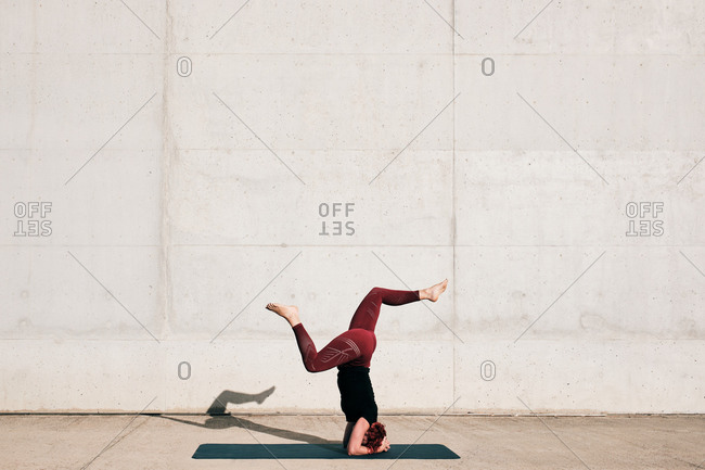 Side view of barefoot female athlete in activewear standing upside down in sirs asana position with legs raised in split on sports mat training alone on street against concrete wall