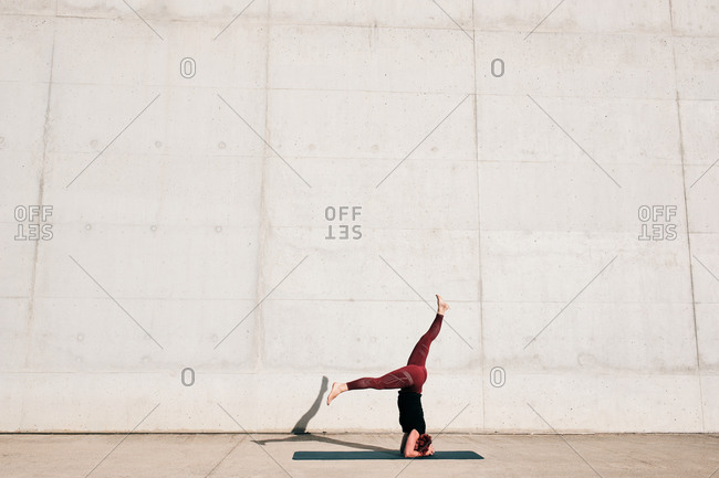 Side view of unrecognizable barefooted female athlete in activewear standing upside down in sirsasana position with legs raised in split on sports mat training alone on street against concrete wall in daytime