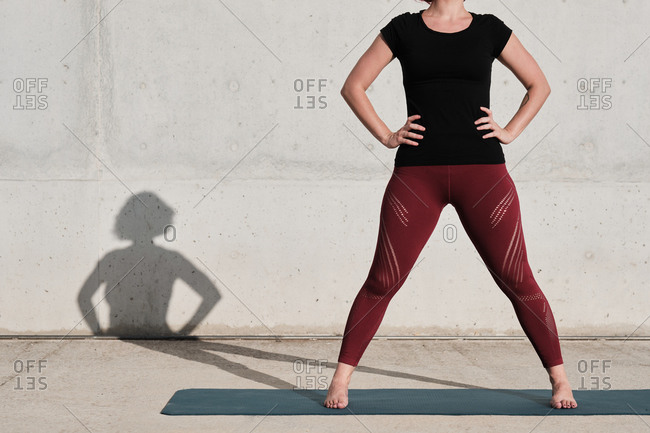 Cropped unrecognizable woman with in sportswear standing on yoga mat against concrete wall after training on the street