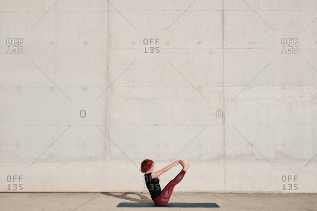 From above side view of unrecognizable barefooted woman with red curly hair in sportswear standing upside down in boat pose on sports mat training alone on street against concrete wall in daytime
