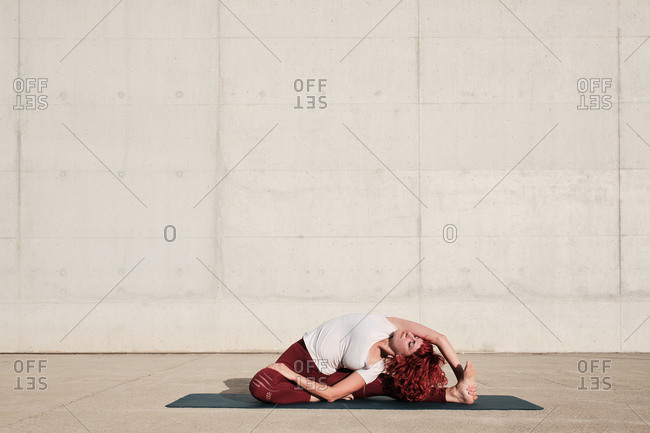 Barefooted woman with closed eyes in sportswear doing yoga revolved head to knee pose on mat training alone on street against concrete wall