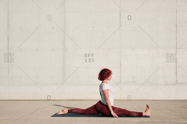 Side view of barefooted woman with closed eyes in sportswear doing yoga in monkey pose on mat training alone on street against concrete wall