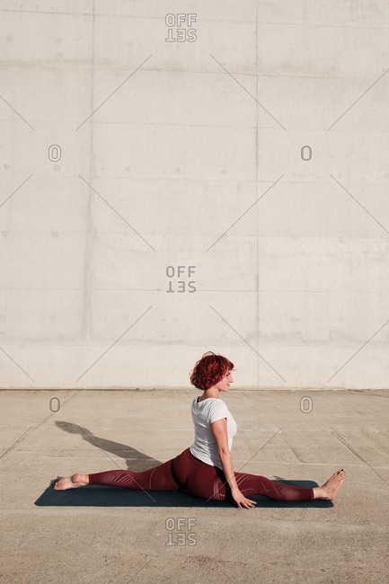Side view of barefooted woman in sportswear doing yoga in monkey pose on mat training alone on street against concrete wall