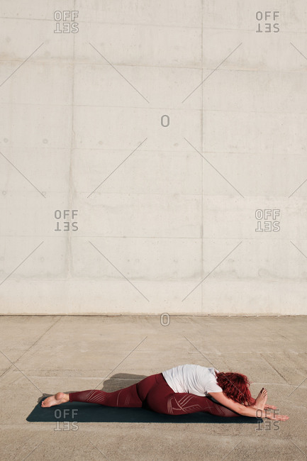 Side view of anonymous barefooted woman in sportswear doing yoga in monkey pose forward bend pose on mat training alone on street against concrete wall