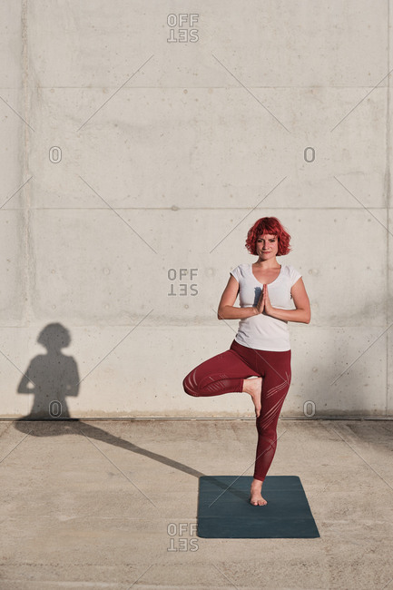 Confident barefooted female athlete in sportswear meditating while standing in vrikshasana position with hands closed to the chest in namaste on sports mat training alone on street against concrete wall in sunlight