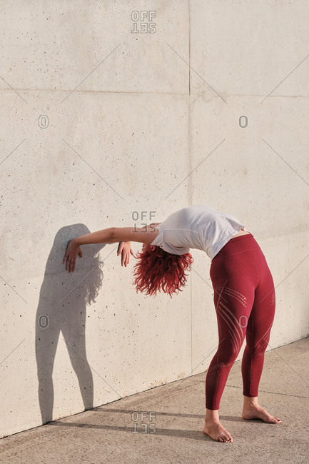 Slim barefooted female with red hair in sportswear standing upside down in downward facing dog pose leaning on concrete wall while training alone on street