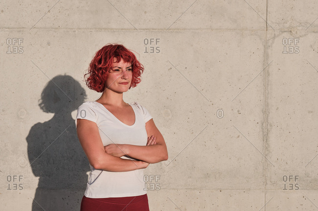 Fit serious woman with curly red dyed hair in sportswear looking away and contemplating while standing with arms crossed against concrete wall after training during sunset in city