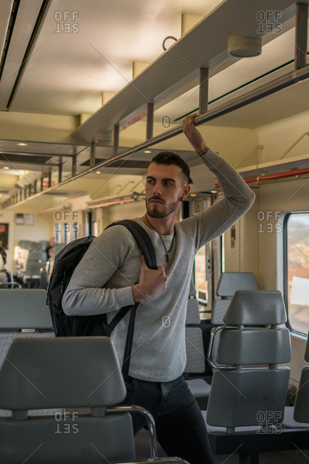 Concentrated young man with backpack holding handrail while standing in empty subway car