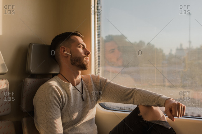 Pensive youthful bearded man with wireless earphones listening to music in train in sunny day