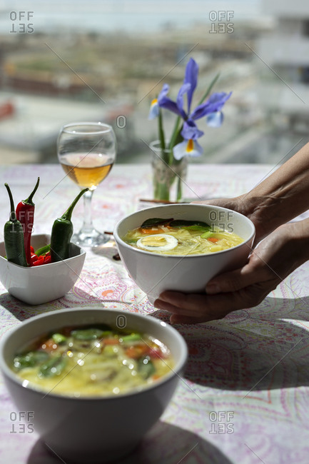 From above cropped unrecognizable person holding a bowl of oriental ramen healthy noodles soup with shiitake, spinach, carrots, eggs and chilies on restaurant table