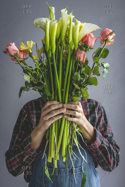 Unrecognizable female professional florist making bouquets of various types. Roses. Yellow flowers. Coves