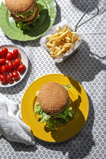 From above top view homemade healthy vegan green lentil burger with tomato, lettuce and French fries