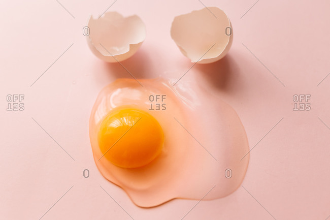 From above raw broken egg with yellow yolk and eggshells on pink background
