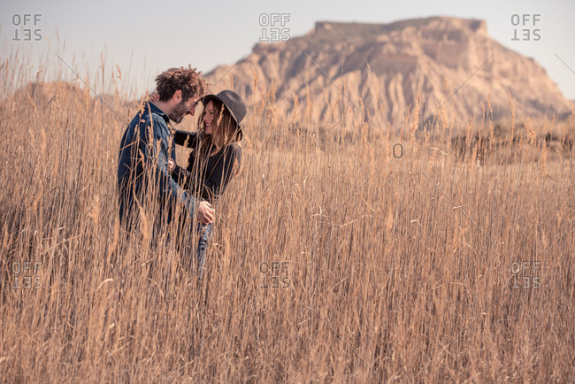 Side view of young man and woman in casual clothes smiling and embracing each other while standing in tall dry grass near mountain in Bardenas Reales in Navarre, Spain