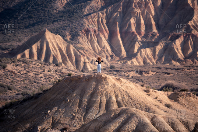 Back view of anonymous female in hat standing on top of stony hill and admiring badlands of Bardenas Reales in Navarre, Spain