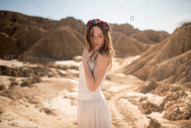 Side view of young woman in white dress and floral wreath touching hair and looking away while standing against rocky hills on sunny day in Bardenas Reales in Navarre, Spain