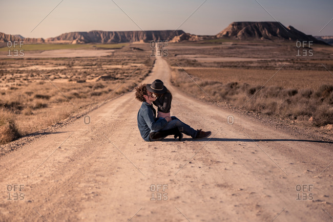 Side view of young man and woman in casual clothes sitting on dry road and kissing during trip in Bardenas Reales in Navarre, Spain