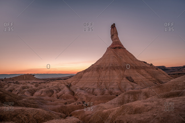 Stony mountain peak located in dry terrain against sundown sky in evening in Bardenas Reales in Navarre, Spain