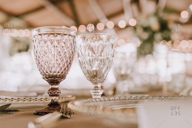 Beautiful empty wineglasses on banquet table on blurred background in modern restaurant