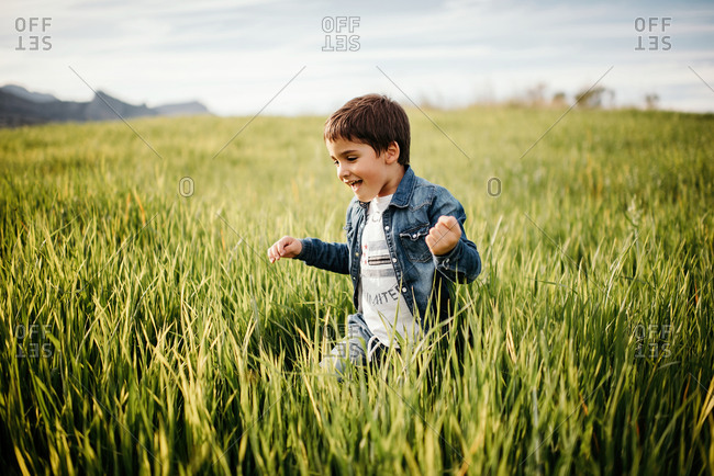 Cheerful little child in denim walking in tall green grass field in rural area in cloudy day