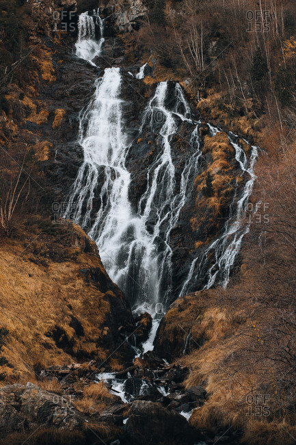 Picturesque view of cascade falling in river from cliff between dry plants
