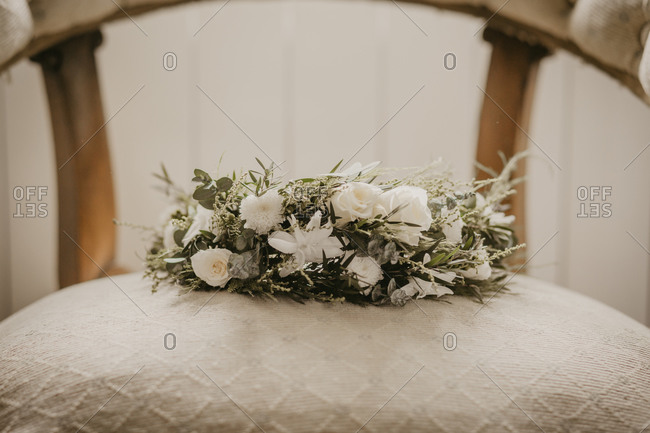 Bunch of elegant flowers placed on soft while chair during wedding celebration
