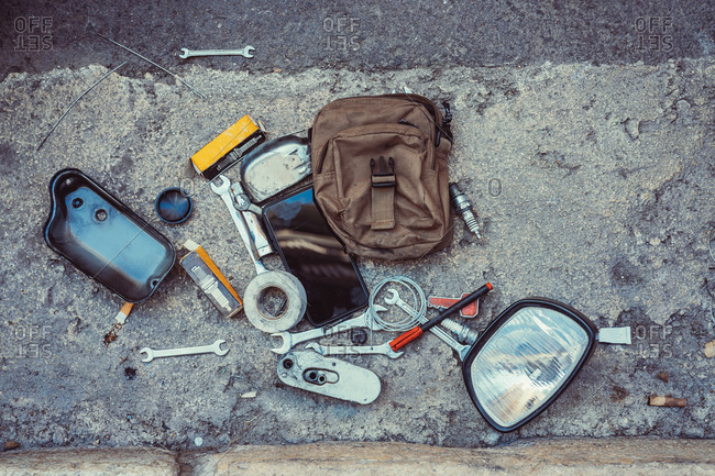 Top view of various repair tools placed on shabby asphalt near bag and motorcycle mirror on city street
