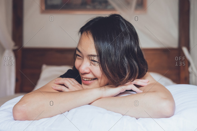 Optimistic Asian woman looking away lying on comfortable bed and laughing while lying on bed in morning at home