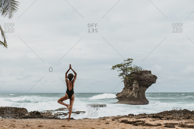 Back view of faceless female tourist in black swimsuit balancing on one leg with arms raised above head on empty seashore in storm