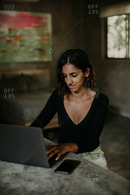 Serious focused youthful ethnic female typing on laptop while sitting at table on table kitchen modern marble countertop