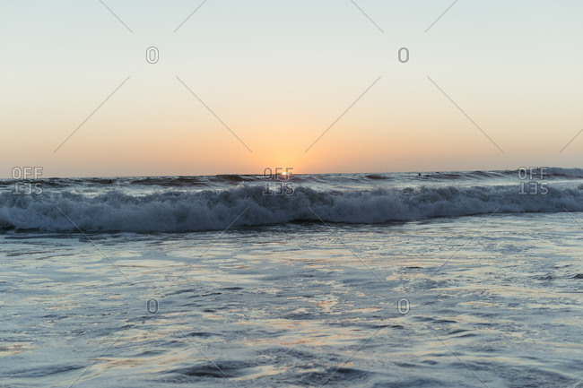Picturesque scenery of colorful sundown and waves on sea in summer evening